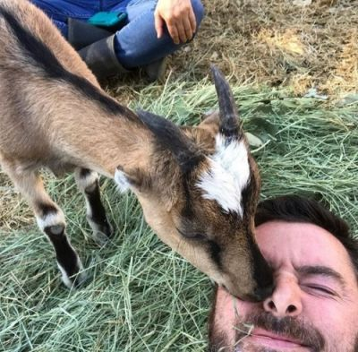 Louie the goat giving Animal Place's Rescue Ranch caregiver